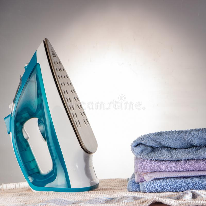 Blue iron and shirt on ironing board shirt household appliance electric concept. Blue iron and shirt on ironing board iron board clothes ironing shirt household stock photography