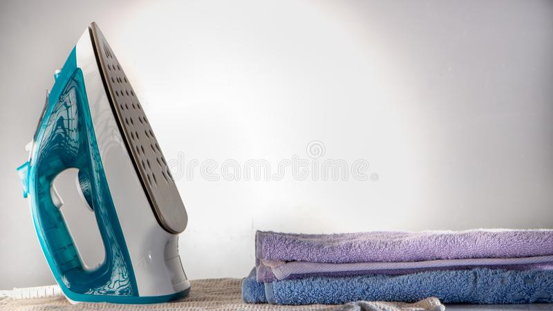 Blue iron and shirt on ironing board shirt household appliance electric concept. Blue iron and shirt on ironing board iron board clothes ironing shirt household royalty free stock photos
