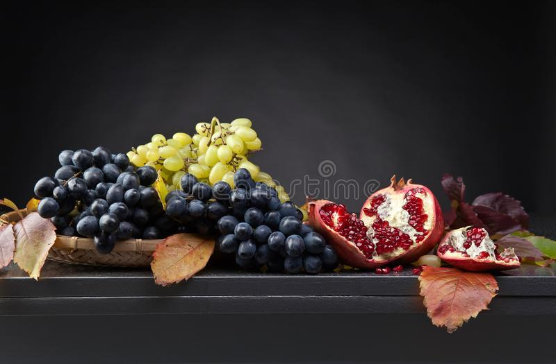 Blue and green grapes with pomegranate royalty free stock images