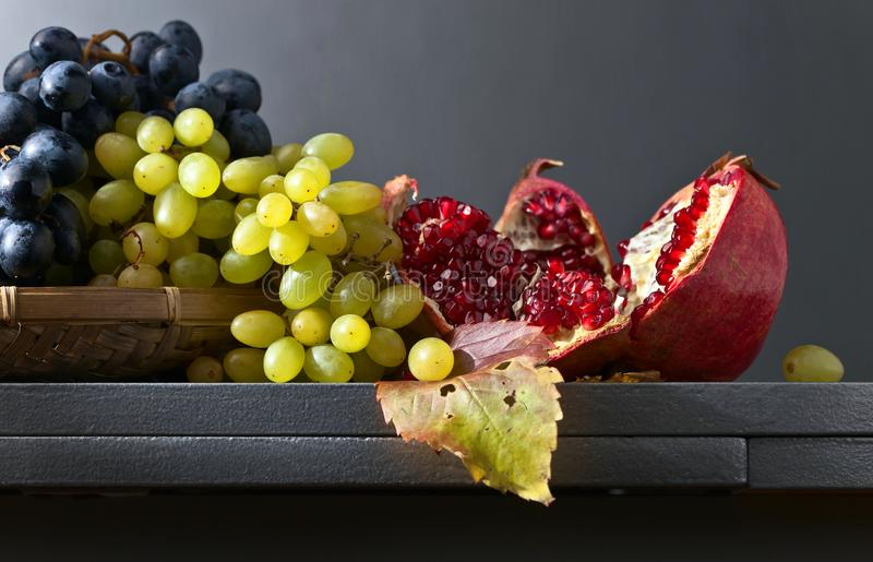 Blue and white grapes with pomegranate stock photos
