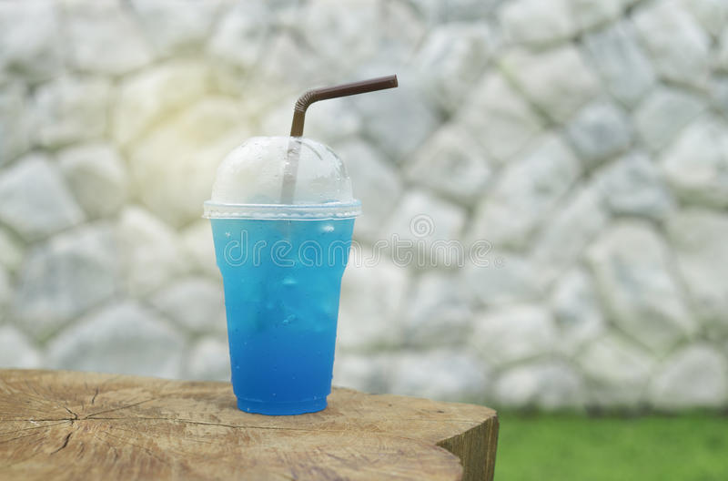 Blue italian soda in takeaway cup on wood table with blurred white stone wall and green grass in background,selective focus. Light effect on a cup stock photos