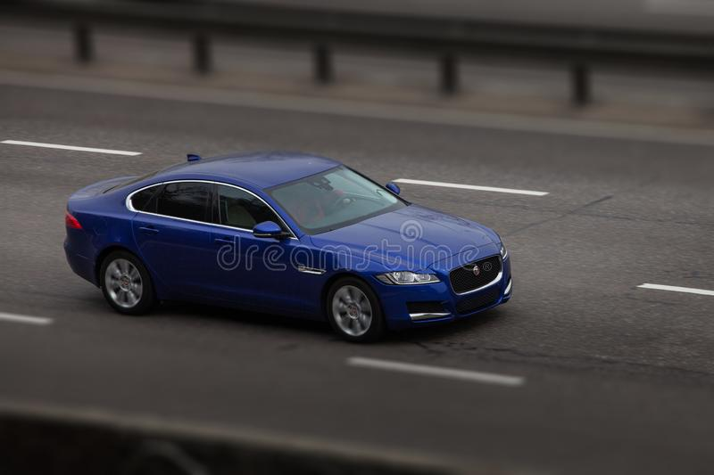 Blue jaguar rides on the road. Against a background of blurred trees royalty free stock photos