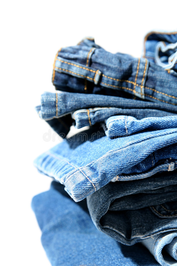 Blue jeans. Pile of trousers made of blue denim jeans stock photos