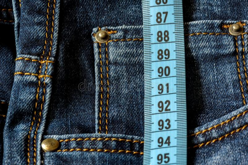 Blue jeans and a blue measuring tape close-up. Measurement of size. royalty free stock photos