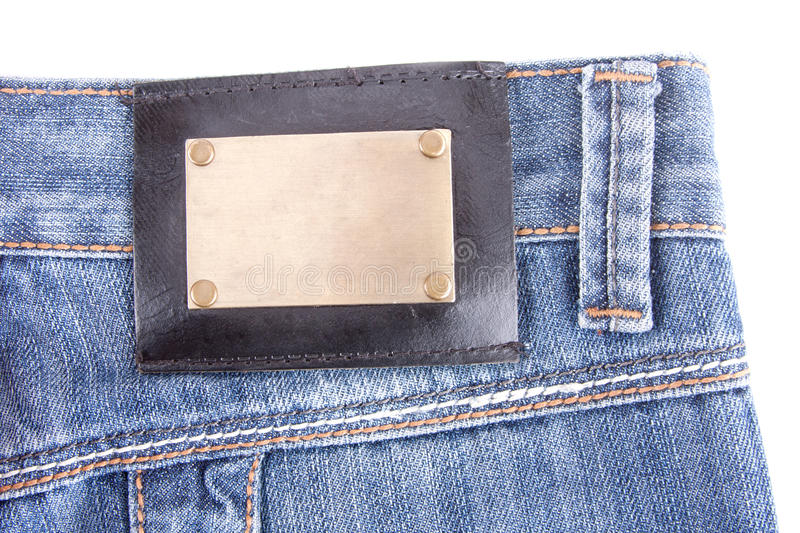 Blue jeans with bronze label. Isolated royalty free stock images