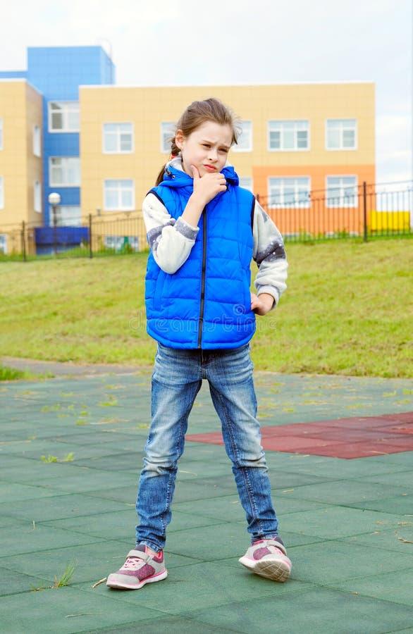 Blue jeans d'uso della bella bambina con il rivestimento senza maniche e le scarpe da tennis che stanno all'aperto fotografia stock