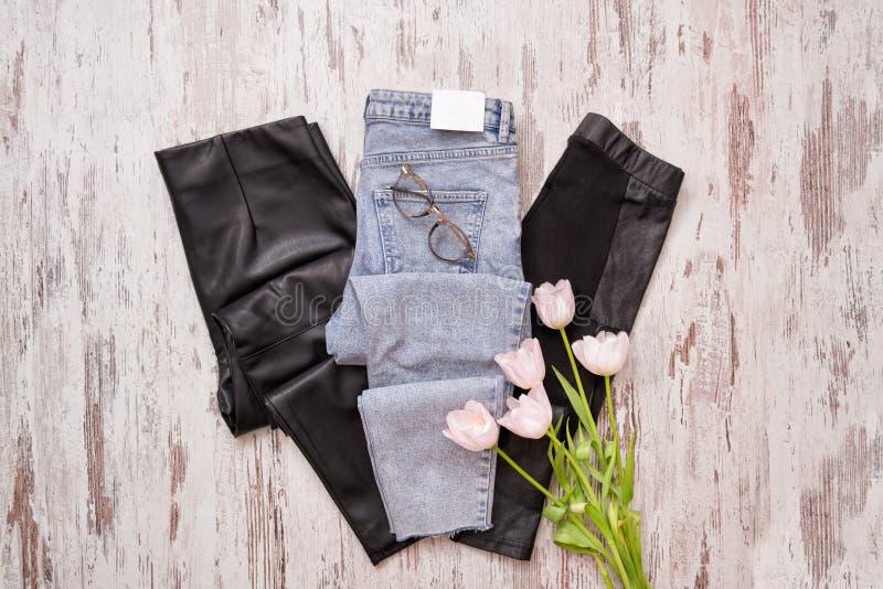 Blue jeans e ghette di cuoio nere, vetri, tulipani rosa Fas fotografia stock