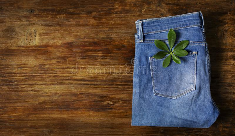 Blue jeans folded. Lie on a wooden table with a green leaf in your pocket stock image