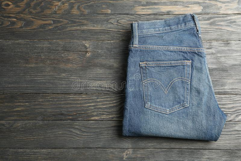 Blue jeans folded on a wooden background. Space for text royalty free stock image