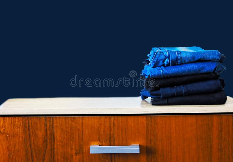 Blue jeans isolated on blue background. Jeans stacked on a light background. Jeans background. Stack of clothing  close up. Blue jeans isolated on blue royalty free stock images