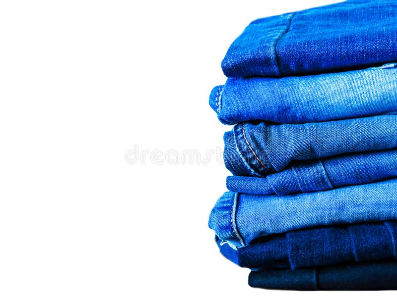 Blue jeans isolated on white background. Jeans stacked on a light background. Jeans background. Stack of clothing  close up, top v stock photography