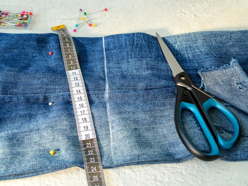 Blue jeans with large hole folded in half, multi colored sewing pins in a box, white tailor tape with centimeters and inches. And scissors. Shorten the jeans royalty free stock photography