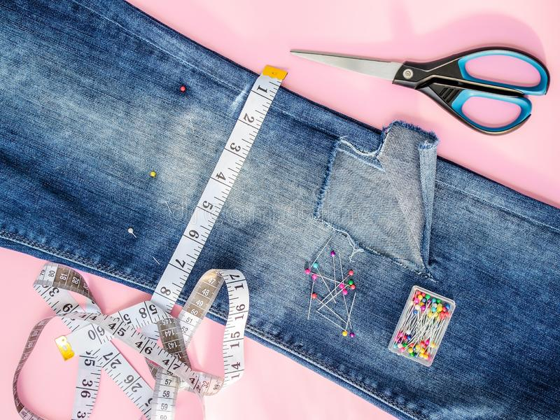 Blue jeans with large hole folded in half, sewing pins in a box, white tailor tape with centimeters and inches and scissors. Shorten the jeans. DIY shorts out stock photography