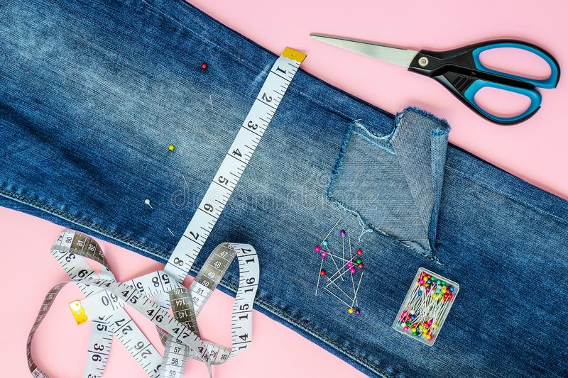 Blue jeans with a large hole on a pant leg below the knee are folded in half and pinned with tailor pins. White tailor tape with centimeters and inches at a stock image