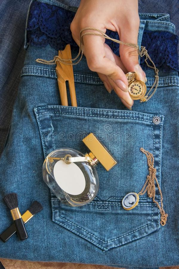 On blue jeans lie a perfume bottle, a gold filigree work clock - stock photo