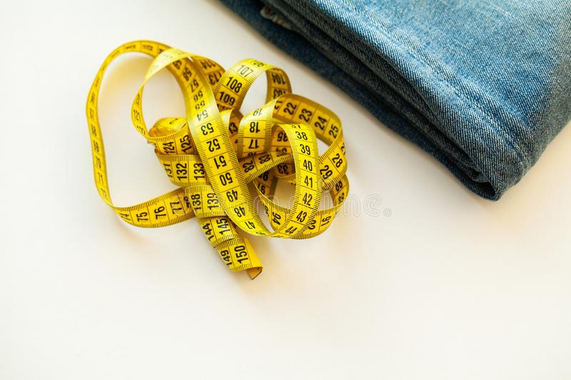 Blue jeans and measuring tape on white background.  royalty free stock image