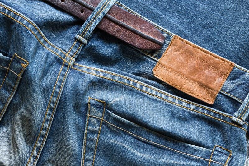 Blue Jeans mit Ledergürtel und Tag lizenzfreie stockfotografie