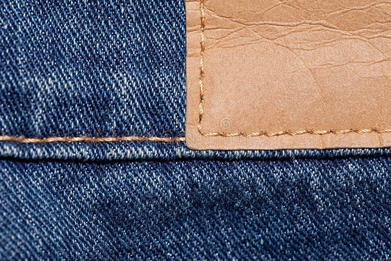 Blue Jeans mit ledernem Stricker stockbilder