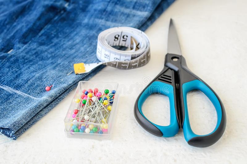Blue jeans shorts, roll of tailor tape with centimeters and inches, multi coloured headed sewing pins in a box and scissors. stock photo