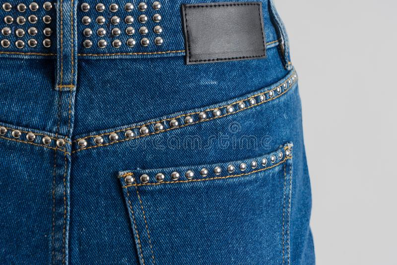 Blue jeans skirt decorated with metallic rivets. Blue jeans skirt decorated with metallic rivets and empty label on. White background stock photography