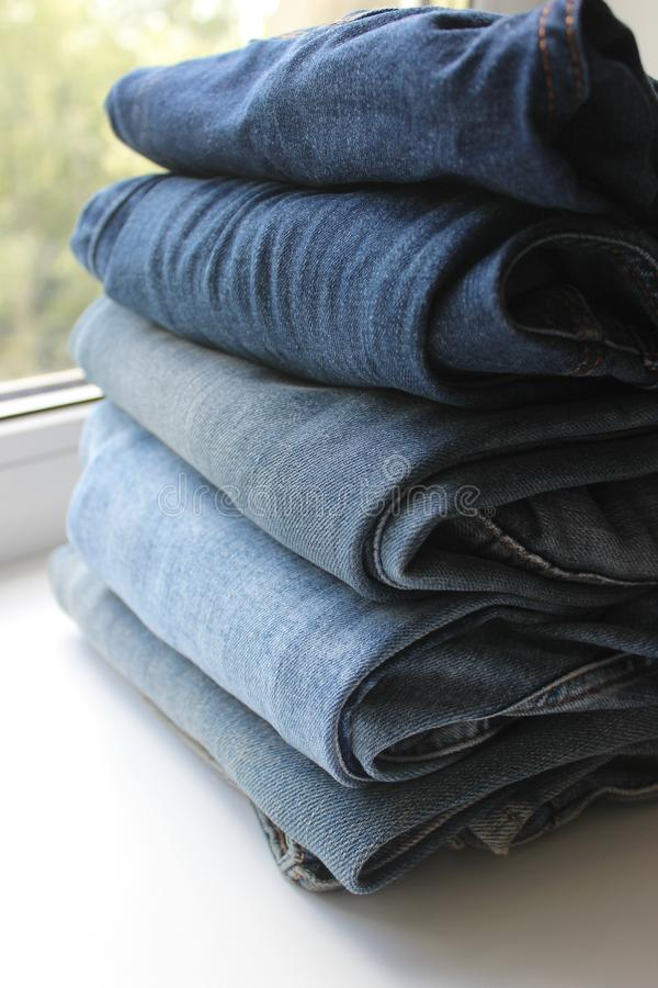 Blue jeans stacked in a pile on white background stock photography