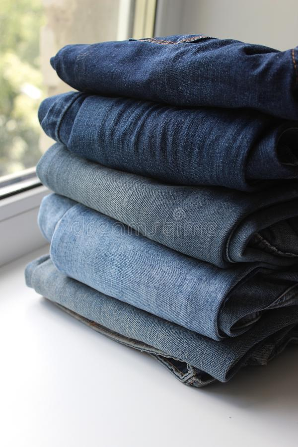 Blue jeans stacked in a pile on white background. A lot of things blue jeans stacked in a pile on white background royalty free stock image