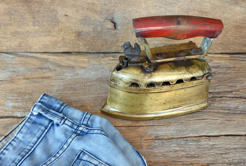 Blue Jeans und Weinlese reden das flache Eisen an, das durch Holzkohle erhitzt wird stockfoto