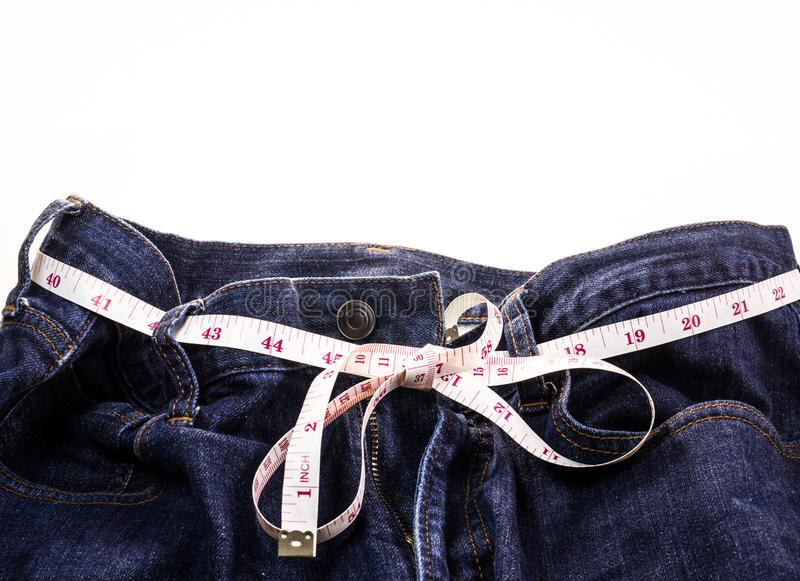 Blue Jeans and white measuring tape on white background. stock photos