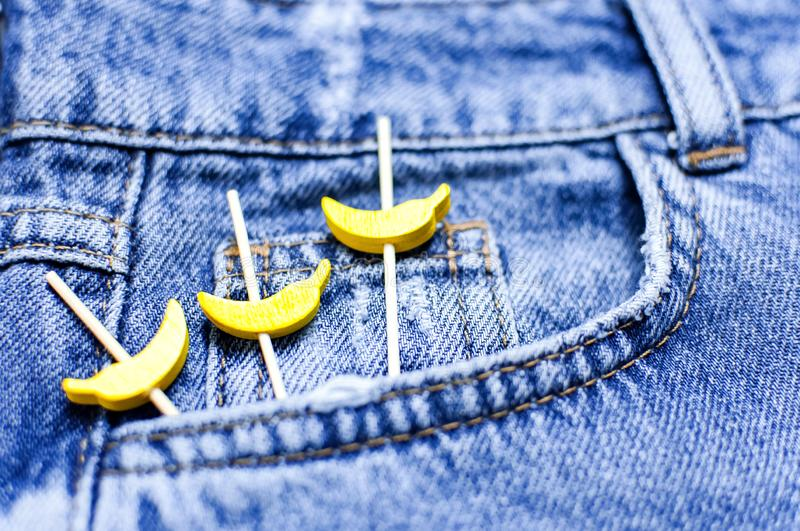 Blue jeans and yellow wooden bananas from a pocket on black background top view flat lay. Detail of nice blue jeans. Jeans texture royalty free stock photo