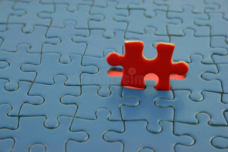Blue Jigsaw with red piece. Close up of a Jigsaw stock images