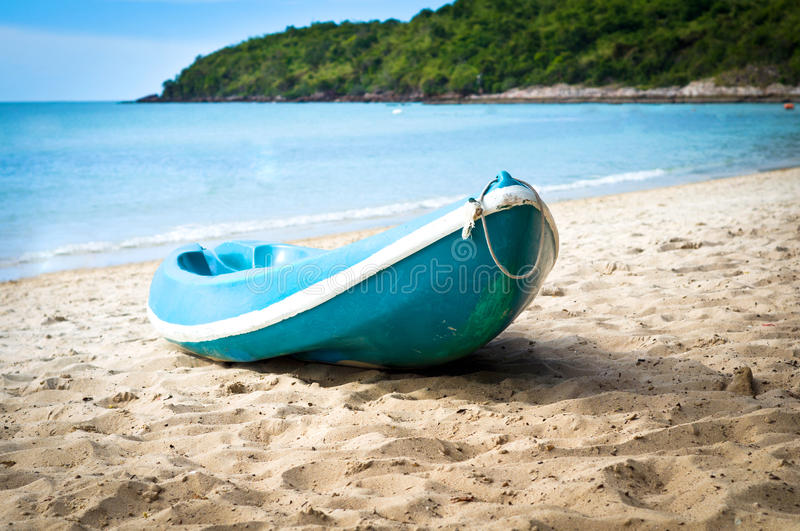Blue kayak on sandy beach royalty free stock images