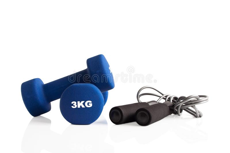 Pair of dumbbells and a skipping rope. Blue 3kg dumbbells and a skipping rope for fitness training royalty free stock images