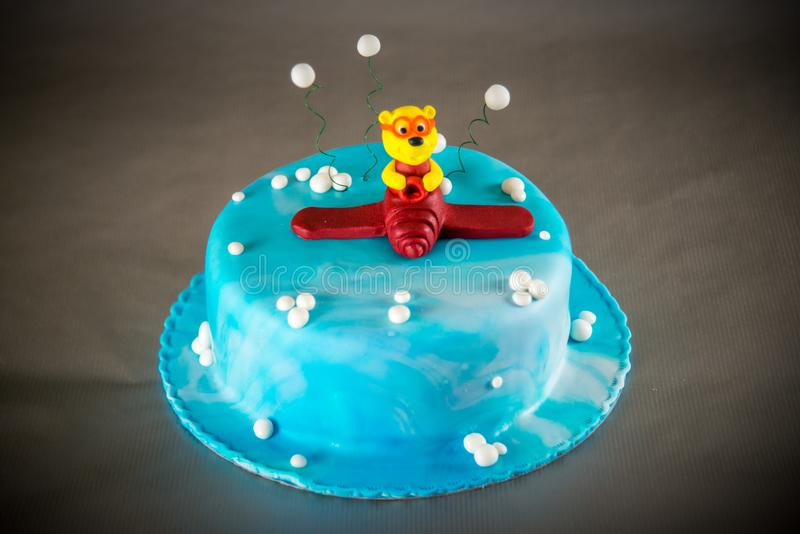 Blue kids birthday cake. Decorated with plane toy on grey background royalty free stock photography