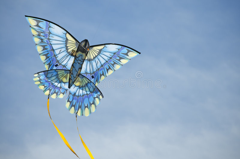 Blue kite arcs across the sky stock photo