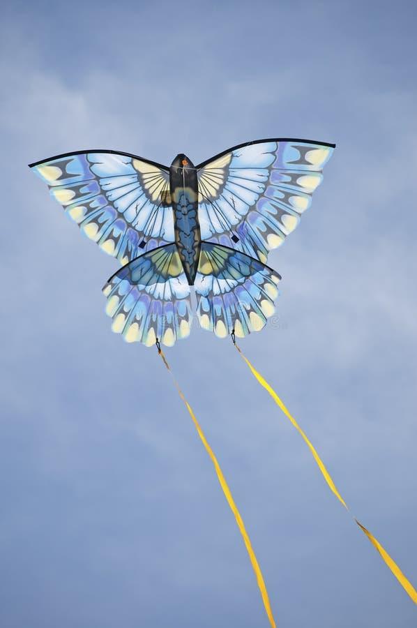 Blue kite racess across the sky royalty free stock photography