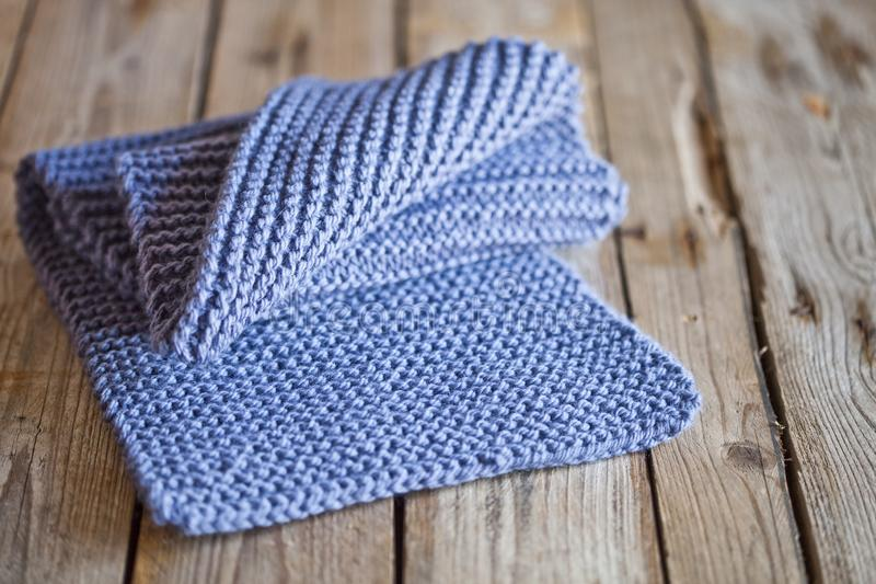 Blue knitted wooden scarf. On wooden background royalty free stock photography
