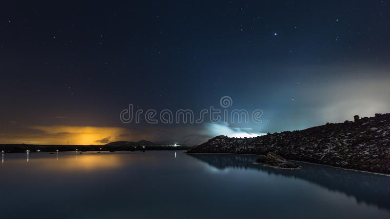 The Blue Lagoon on a calm night. The Blue Lagoon lake on a calm night with the light pollution from the capital, Reykjavik, lighting up the clouds on the horizon stock image