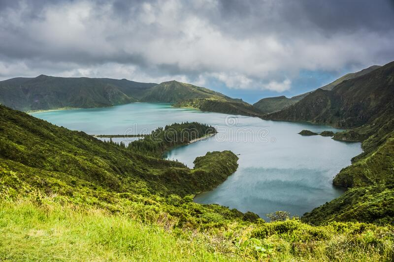 Blue Lake Behind Green Mountain Under White Clouds stock image