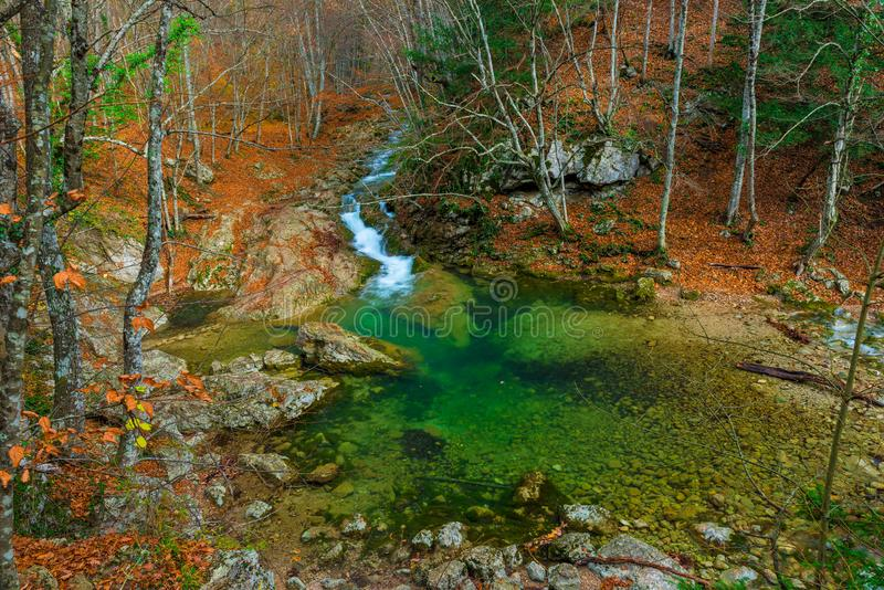Blue lake and mountain stream flowing in a canyon in the mountains in the autumn afternoon stock image