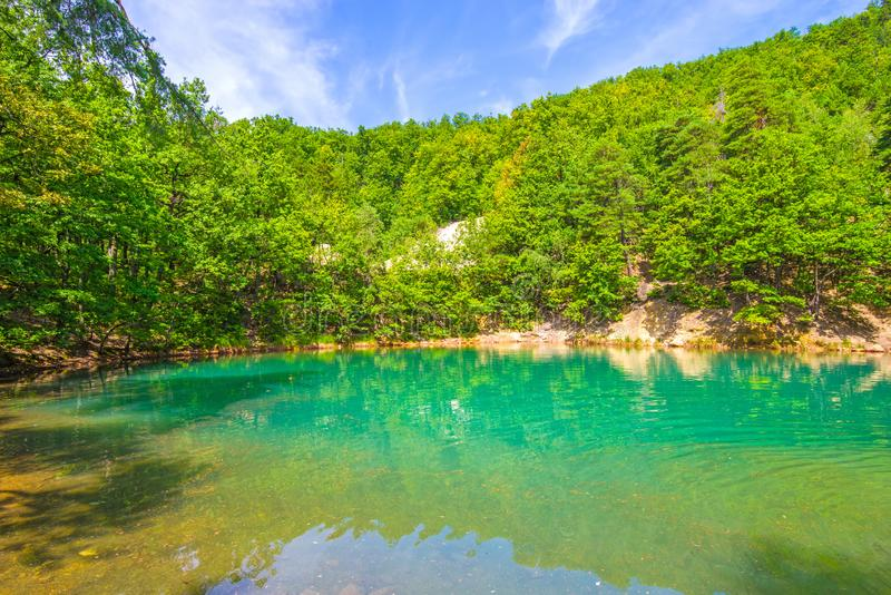 Green lake in summer forest. The Blue Lake from Romania change its color depending the light: from blue to emerald green. It resulted from the collapse of mine royalty free stock photo