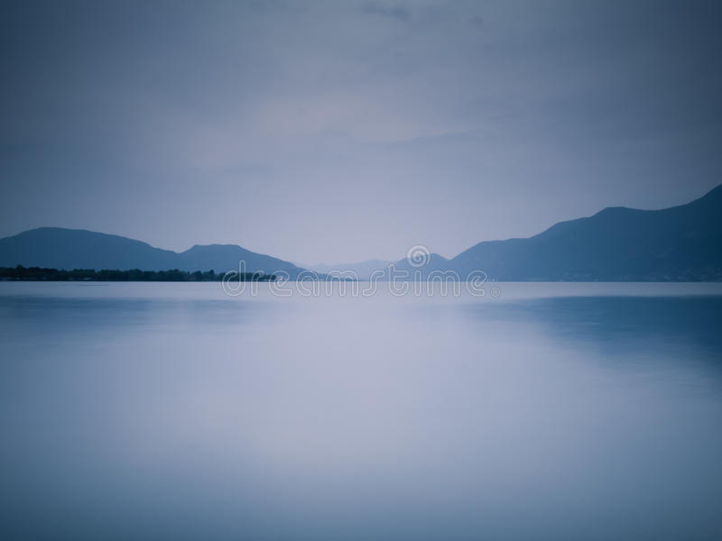 Blue lake at twilight. Still blue lake at twilight, with blue dominant color. The place is Iseo lake, Italy royalty free stock photography
