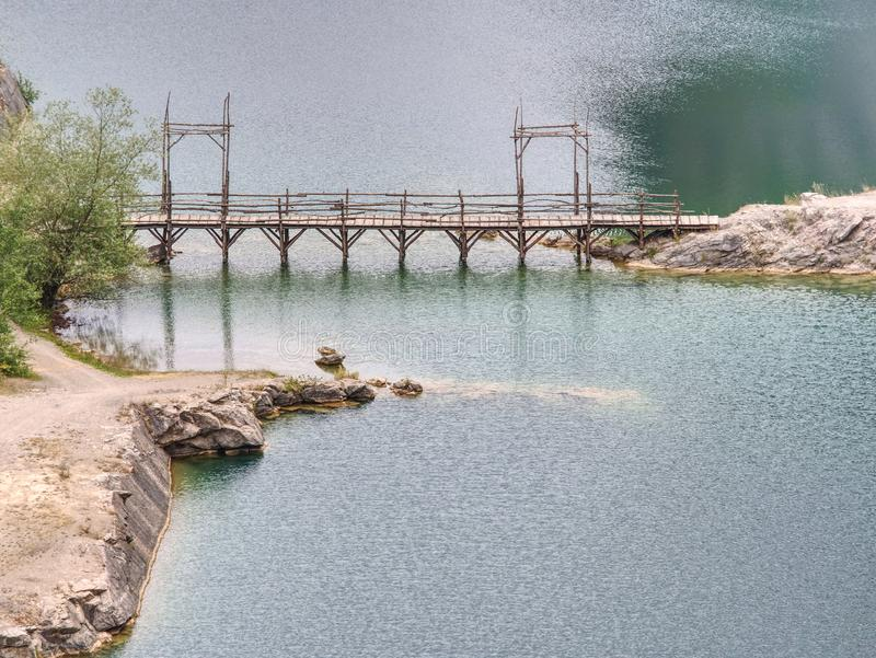 Blue lake with wooden tourist path bridge above cold water. Green blue lake with wooden tourist path bridge above cold water. Hiking in the national park, woods stock photography