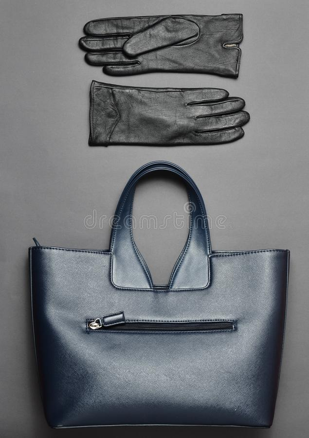 Blue leather handbag and gloves on a gray background. Top view. Flat lay. Seasonal female accessories royalty free stock photography