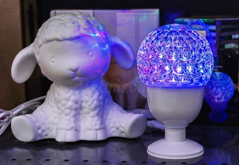 Blue LED lamp and a lamb figurine in the interior of a children`s room.  stock photos