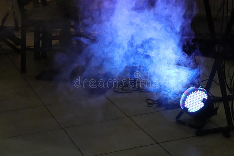 Blue LED spotlight on the floor with smoke in dark room close to cables and pillars with copy space. royalty free stock images