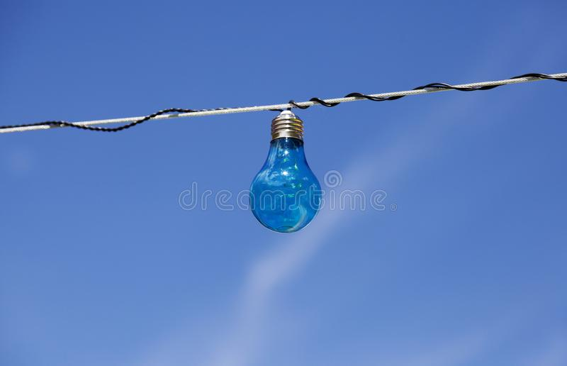Blue light bulb with blue summer sky royalty free stock photo