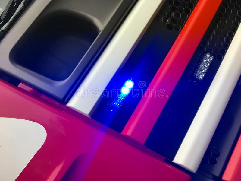 Blue light of a fire truck. Close up of a fire engine. Blue, red, white and black colors and diagonal lines stock image
