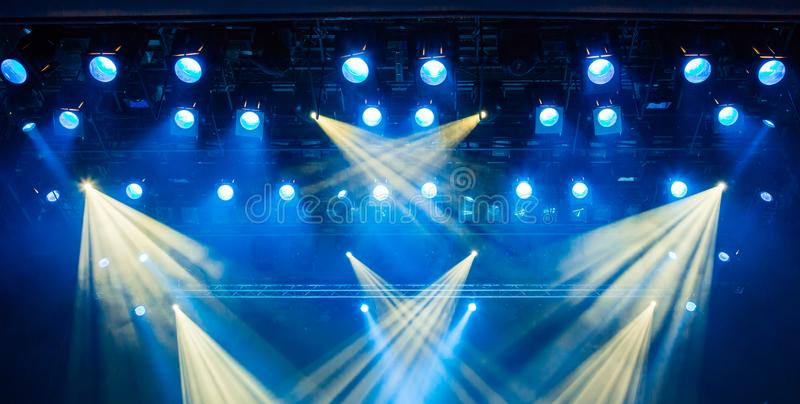 Blue light rays from the spotlight through the smoke at the theater or concert hall. Lighting equipment for a performance or show stock images