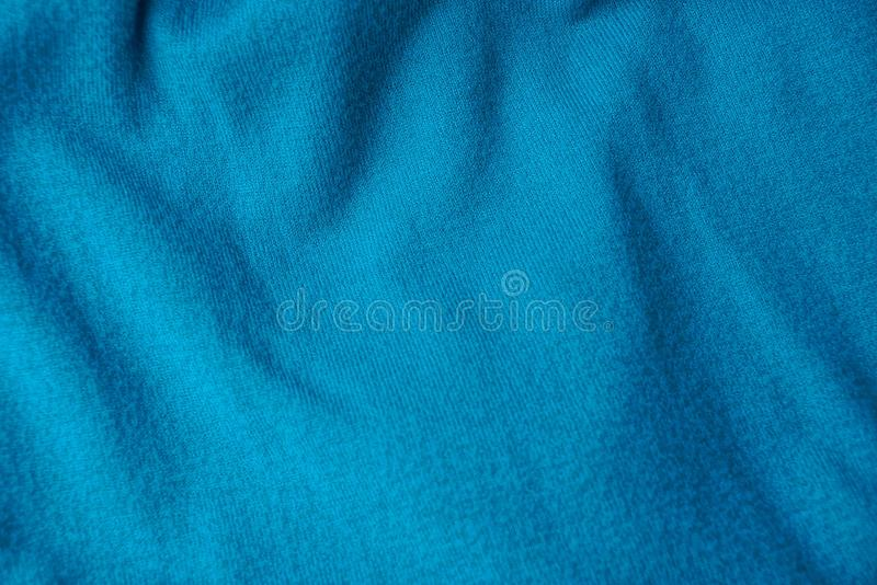 Turquoise woolen texture from a fragment of crumpled clothes. Blue light woolen texture of a fragment of crumpled clothes royalty free stock photos