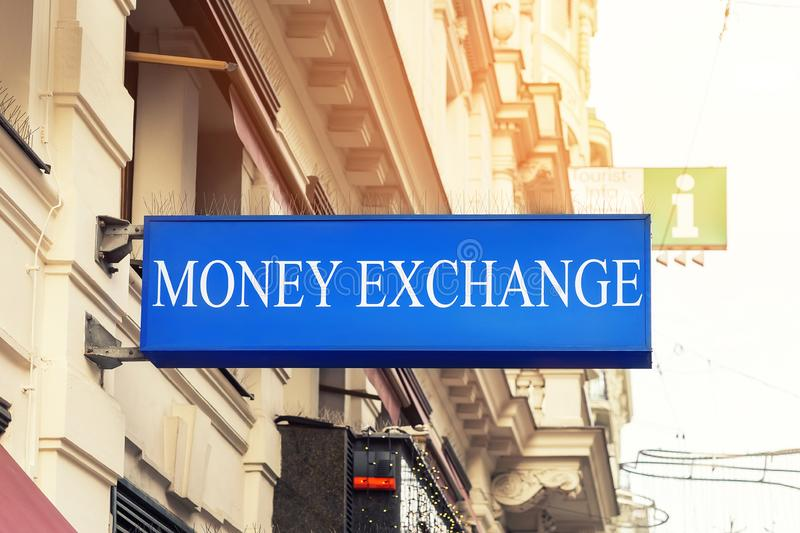 Blue lightbox singnboard Money exchange office in old historical city center. Touristic financial services. Currency finance business sign dollar euro economy stock images